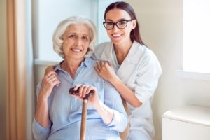 Helpful. Smiling and cheerful senior woman with her kind nurse